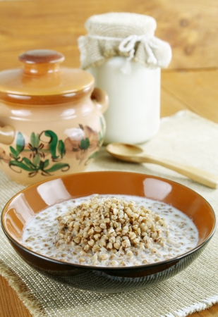 A bowl of buckwheat porridge and milk on a wooden table photo