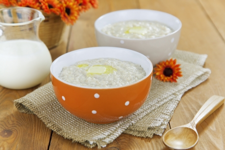 Oatmeal porridge with butter in bowl on wooden table Stock Photo