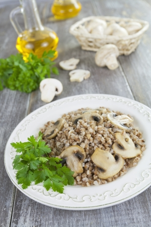 grits: Buckwheat with mushrooms in a bowl on a wooden table