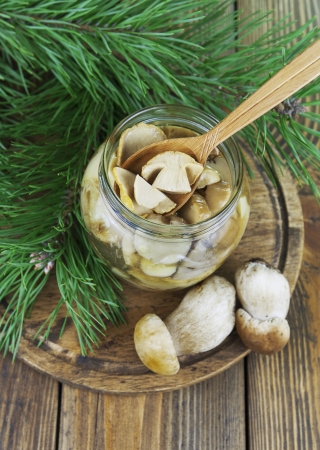 Pickled mushrooms in a glass jar on a wooden table photo