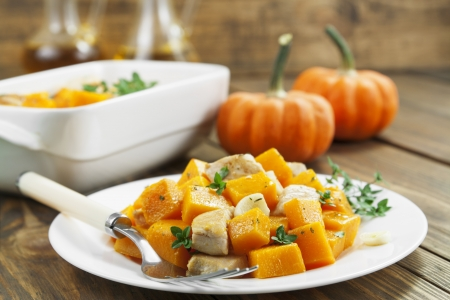 Pumpkin, baked with chicken, garlic and herbs on the plate Stock Photo