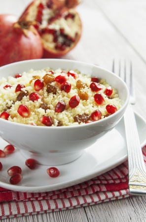 Couscous with pomegranate, raisins and spices in white bowl on the wooden table photo