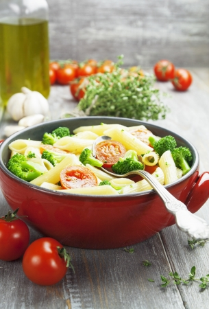 Penne pasta with broccoli and cherry tomatoes on the table photo