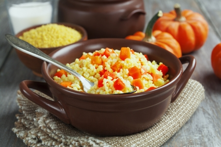 Millet porridge with pumpkin and milk in a pot on the table photo