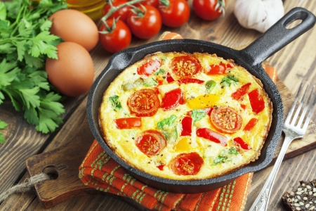 Omelet with vegetables and cheese. Frittata in a frying pan  photo