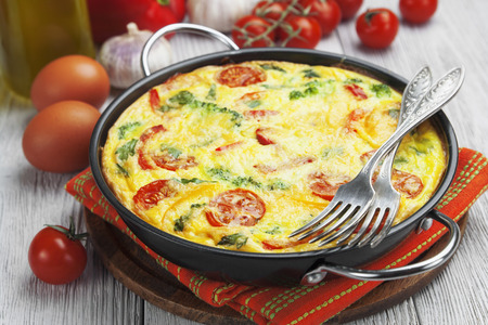 Omelet with vegetables and cheese. Frittata in a frying pan  Stock Photo