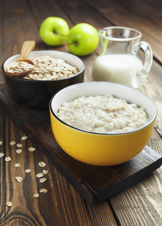 Porridge, oats, milk and green apples on the table Stock Photo