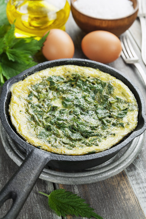 fried egg: Omelet with nettles in the pan on the wooden table  Stock Photo