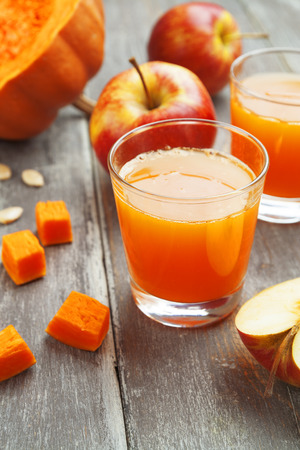 Juice of apples and pumpkins in the glasses on the table photo