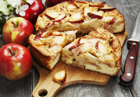 Apple pie and red apples on a wooden table Banque d'images