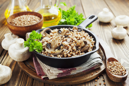 Buckwheat porridge with mushrooms in the frying pan on the table