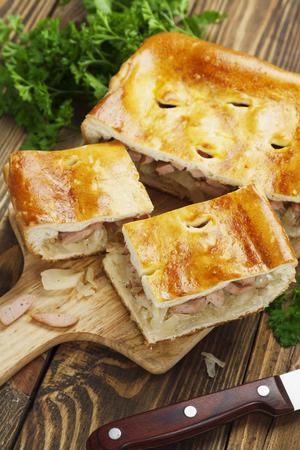 Pie with cabbage and sausages on the table photo