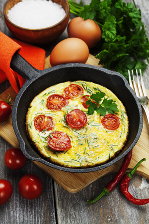 Scrambled Fried eggs with tomatoes in a cast iron pan on the table photo