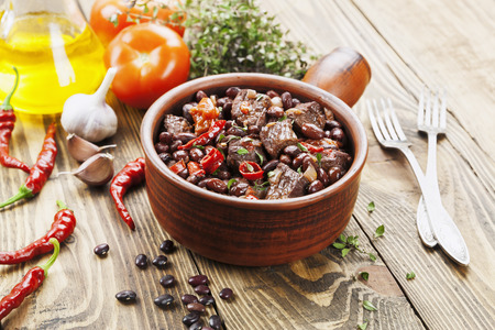 Meat stew with red beans and chili pepper on the table
