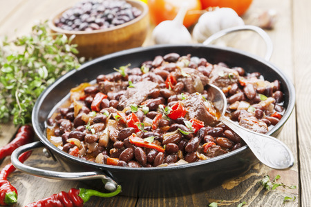 rustic food: Meat stew with red beans and chili pepper on the table Stock Photo