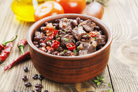 meat dish: Meat stew with red beans and chili pepper on the table Stock Photo