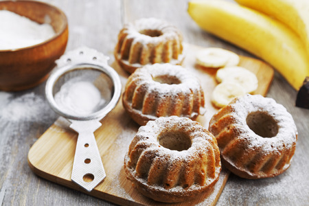 Homemade banana cupcake with powdered sugar on the wooden table photo