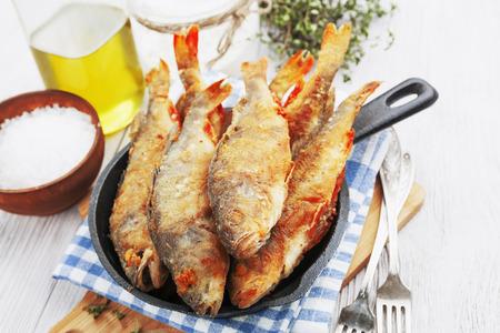 pescado frito: Pescado frito en una sartén en la mesa