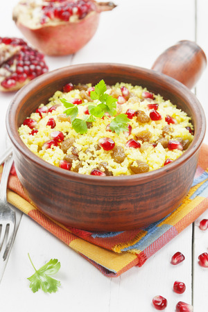Couscous with pomegranate, raisins and spices on the table photo