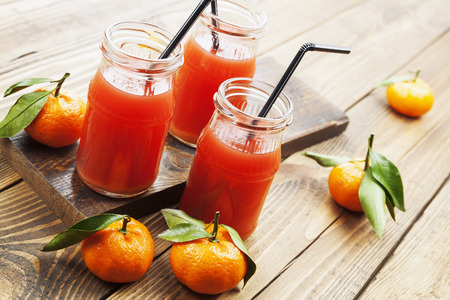 Juice in the bottle and mandarins on the wooden table photo
