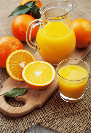 Orange juice  in the glass jug on the wooden table photo
