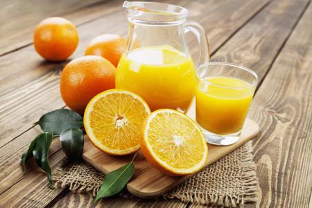 木製のテーブルの上のガラスの水差しでオレンジ ジュース