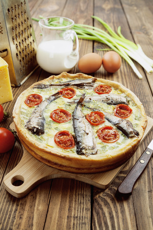 sprats: Quiche with sprats and cherry tomatoes on a wooden table Stock Photo