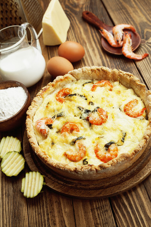Quiche with shrimp and zucchini on a wooden table photo