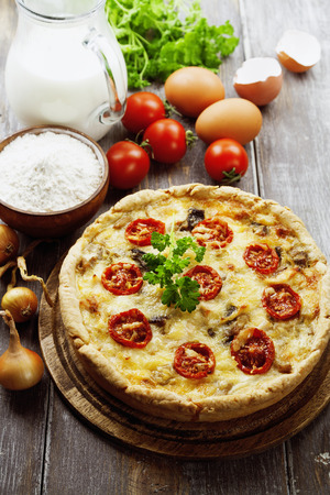 Quiche with chicken, mushrooms and cherry tomatoes on a wooden table photo