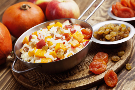 meatless: Sweet pilaf with pumpkin, apples and dried fruit on the table Stock Photo