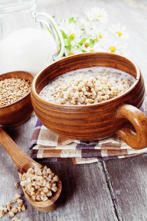 Buckwheat porridge with milk in the bowl on the table photo
