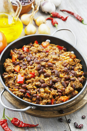 dinners: Chili con carne in the frying pan on a wooden table