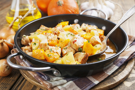 Chicken stew with pumpkin, potatoes and spices on the table Stock Photo