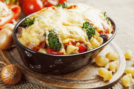 Casserole with meat, pasta, broccoli and tomatoes on the table