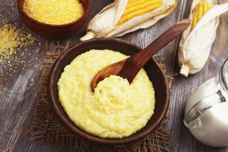 corn flour: Fresh corn meal in the plate on the table Stock Photo