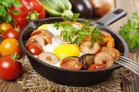 Fried eggs with vegetables and sausage in a pan Stock Photo
