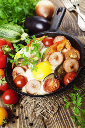 breakfeast: Fried eggs with vegetables and sausage in a pan Stock Photo