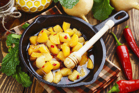 second meal: Fried turnip with honey and pepper in a frying pan Stock Photo