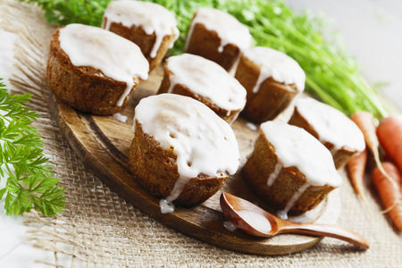 icing: Carrot muffins with icing on the table Stock Photo