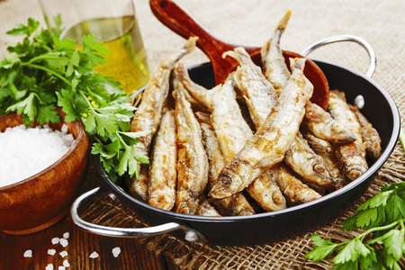 second meal: Fried fish capelin in a pan on the table