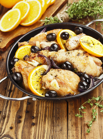 fricassee: Chicken with oranges and olives in a frying pan