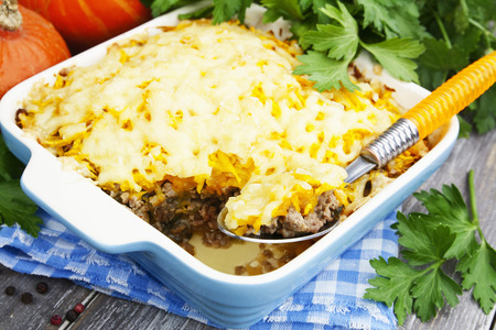 baked meat: Pumpkin casserole with meat and cheese in a ceramic pot Stock Photo