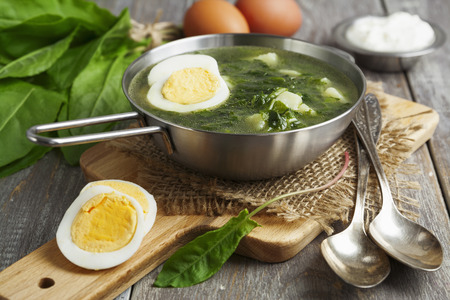 sorrel: Sorrel soup with egg on wooden table