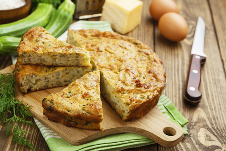 Pie with zucchini, cheese and herbs on the table Stock Photo