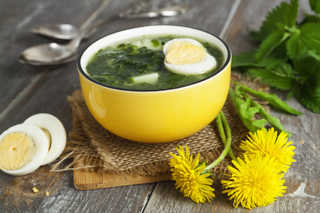 sour grass: Soup of nettles on the wooden table