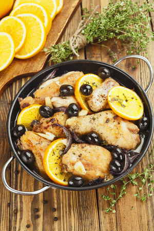 Chicken with oranges and olives in a frying pan
