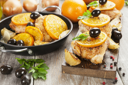 Chicken with oranges and olives on the table Stock Photo