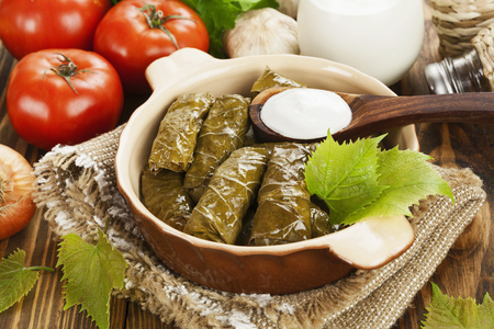 Dolma from grape leaves and minced on the wooden table Reklamní fotografie
