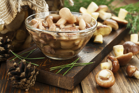 Pickled mushrooms in transparent glass bowl