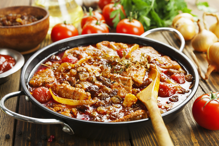 spicey: Pork stew with tomatoes and raisins in a frying pan